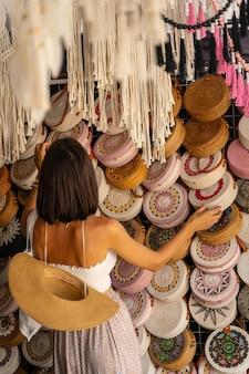 Junge frau kommt in einen lokalen korbwarenladen, um während ihrer reise exotische taschen zu kaufen
