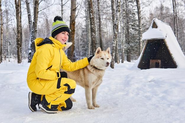Junge frau kommuniziert mit einem heiseren hund im winterwald