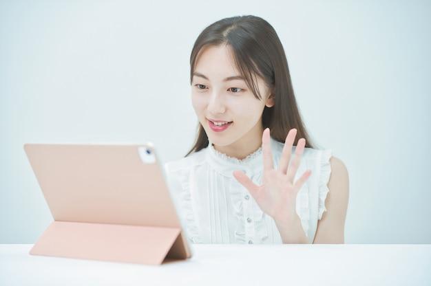 Junge frau kommuniziert online mit einem tablet-pc