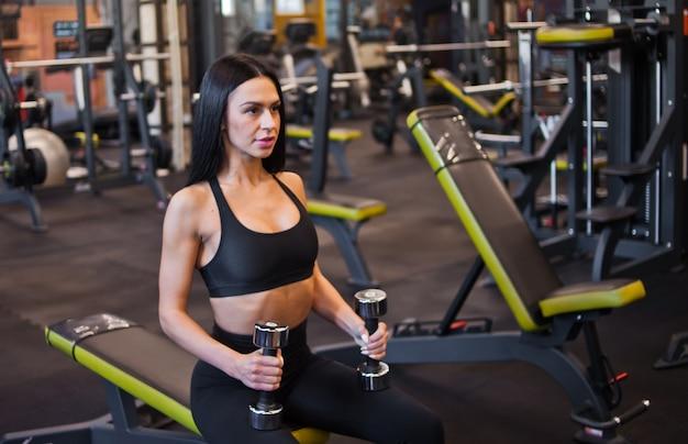 Junge frau konzentriert auf das training hält hanteln in händen, während sie auf einer bank im fitnessstudio sitzen