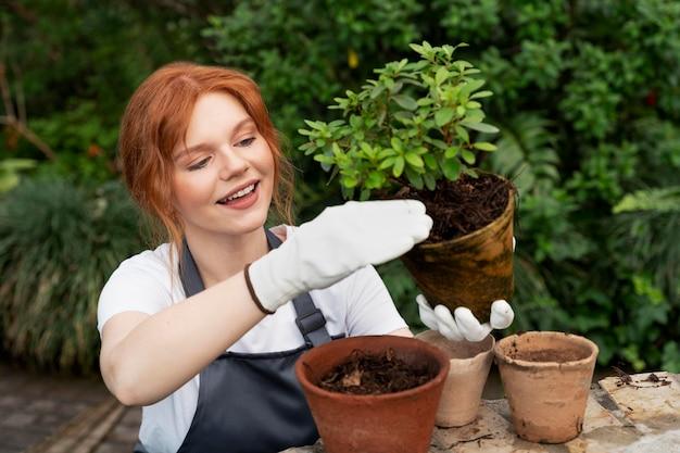 Junge frau kümmert sich in einem gewächshaus um ihre pflanzen