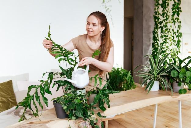 Junge frau kümmert sich um und gießt ihre zimmerpflanzen. pflege von pflanzen zu hause