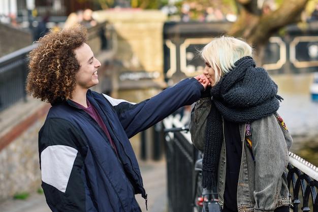 Junge frau küsst die hand ihres freundes in camden town little venice,