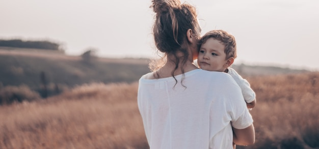 Junge frau küsst ihren kleinen sohn im sonnigen auf der wiese im sonnenuntergang. junge mutter hält ihr baby. mutter und kleiner sohn haben eine gute zeit in der natur. farbiges bild