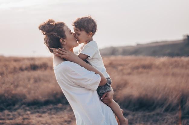 Junge frau küsst ihren kleinen sohn im sonnigen auf der wiese im sonnenuntergang. junge mutter hält ihr baby. mutter und kleiner sohn haben eine gute zeit in der natur.