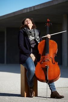 Junge frau lacht glücklich mit ihrem instrument