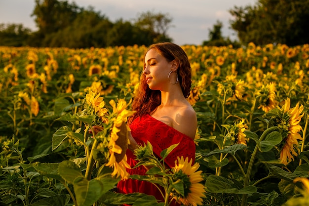 Junge frau lächelt bei sonnenuntergang in einem feld von sonnenblumen