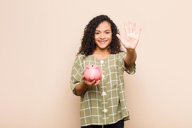 Junge frau lächelt und sieht freundlich aus, zeigt nummer fünf oder fünfte mit der hand nach vorne, zählt herunter und hält ein sparschwein
