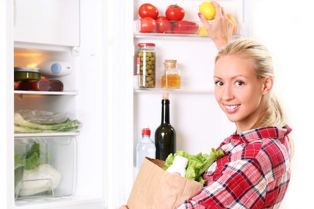 Junge frau legt ein essen in den kühlschrank