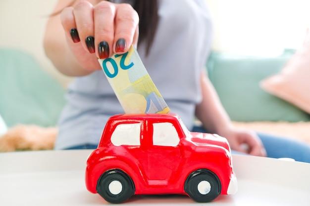 Junge frau legt geld in ein sparschwein und spart für ein auto.