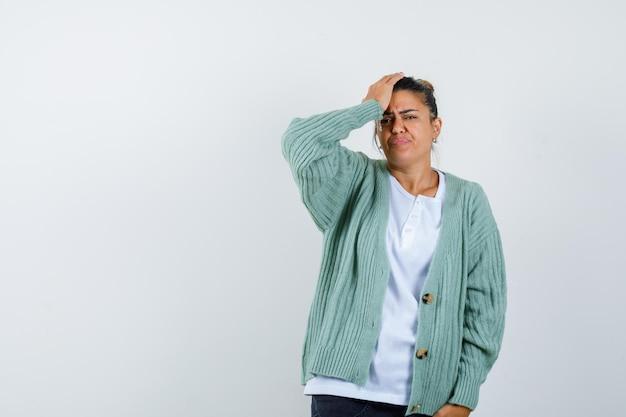 Junge frau legt hand auf die stirn, verzieht das gesicht in weißem t-shirt und mintgrüner strickjacke und sieht genervt aus