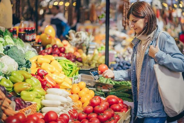 Junge frau legt obst und gemüse in baumwollbeutel auf dem lebensmittelmarkt. wiederverwendbare öko-tasche zum einkaufen. nachhaltiger lebensstil. umweltfreundliches konzept.