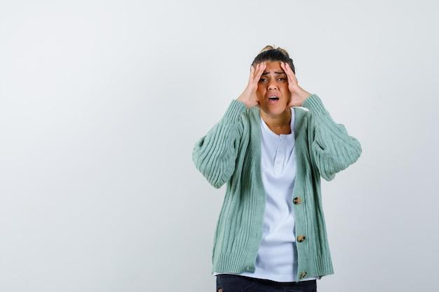 Junge frau legt sich die hände vors gesicht, verzieht das gesicht in weißem t-shirt und mintgrüner strickjacke und sieht genervt aus