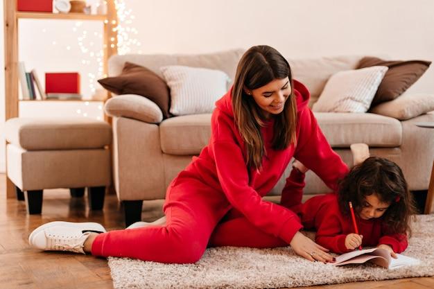 Junge frau lehrt tochter zu schreiben. innenaufnahme des niedlichen kindes, das auf teppich mit stift und notizbuch liegt.