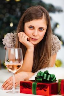 Junge frau liegt auf einer weißen haut mit roten geschenken und einem glas wein vor dem hintergrund eines weihnachtsbaumes