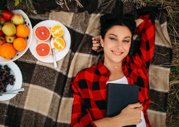 Junge frau liegt auf plaid, draufsicht, picknick im sommerfeld. romantisches junket, schöne ferien
