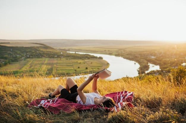 Junge frau liegt auf rotem plaid oben auf dem berg und liest buch über sonnenuntergang mit perfekter landschaft.
