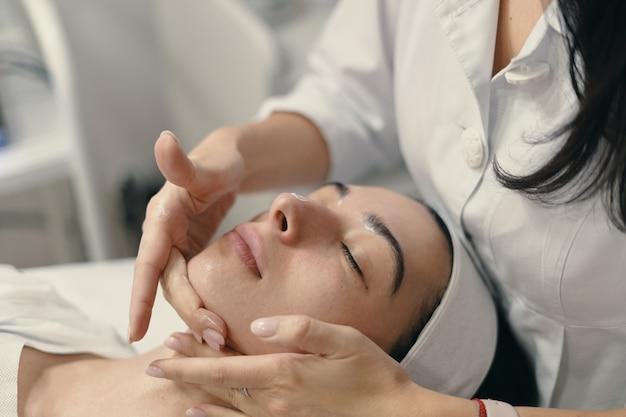 Junge frau liegt mit geschlossenen augen, kosmetikerin macht verfahren
