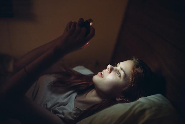 Junge frau liegt nachts mit einem telefon in den händen im bett