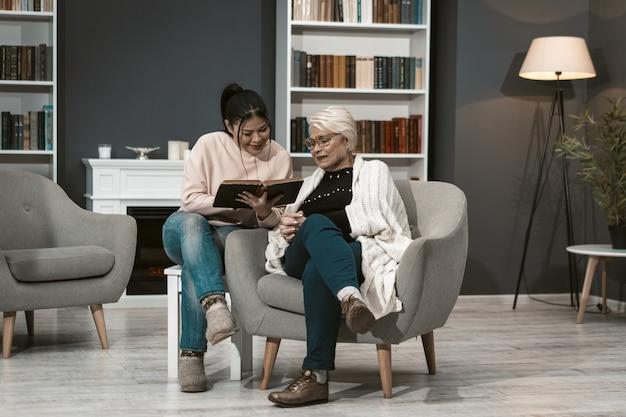 Junge frau liest buch für ihre ältere mutter