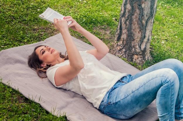 Junge frau liest buch im park liegend auf gras. selektiver fokus junge schöne aufmerksame frau liegt auf grünem gras und liest buch gegen stadtpark.