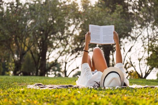 Junge frau liest im park