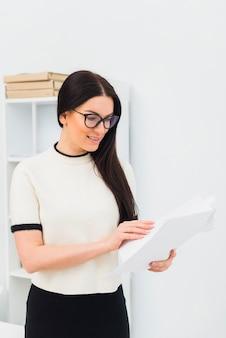 Junge frau liest papiere im büro