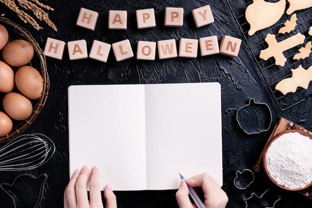 Junge frau liest und schreibt rezept für die herstellung von halloween-keksen, designkonzept für die vorbereitung auf die halloween-party, draufsicht, flache lage, overhead.
