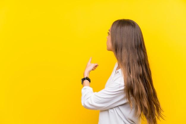 Junge frau lokalisiert auf dem gelb, das zurück mit dem zeigefinger zeigt