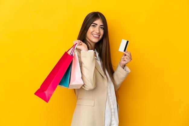 Junge frau lokalisiert auf gelber wand, die einkaufstaschen und eine kreditkarte hält