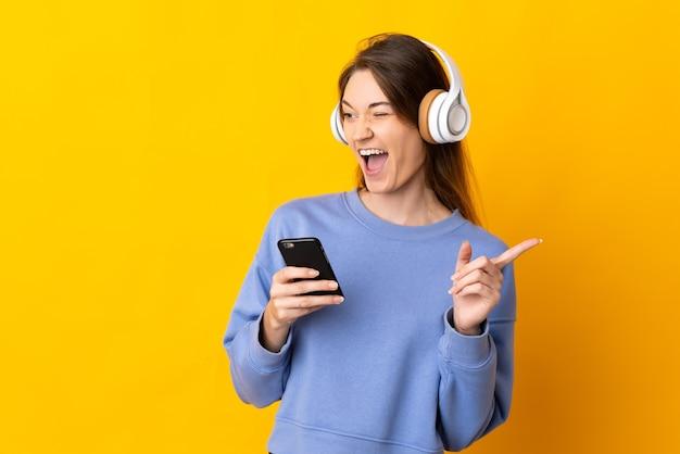 Junge frau lokalisiert auf gelber wand, die musik mit einem handy hört und singt