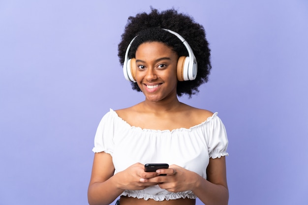 Junge frau lokalisiert auf lila hörende musik mit einem handy und schauender front