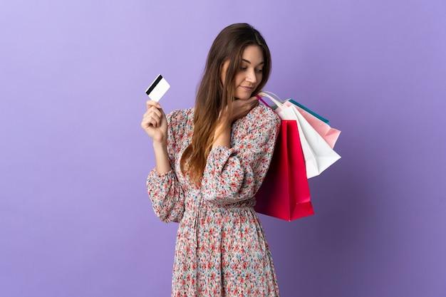 Junge frau lokalisiert auf lila wand, die einkaufstaschen und eine kreditkarte hält