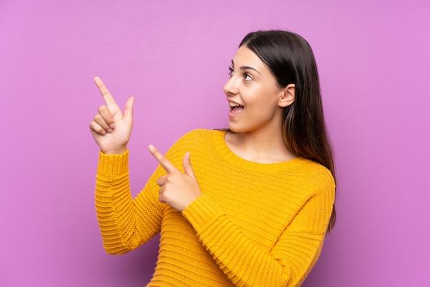 Junge frau lokalisiertes purpurrotes zeigen mit dem zeigefinger eine großartige idee