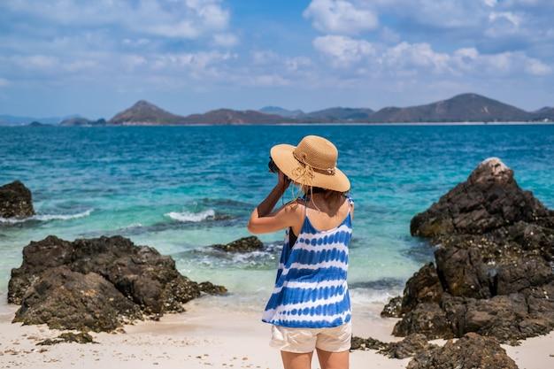 Junge frau machen ein foto am tropischen strand, an den sommerferien und am reisekonzept