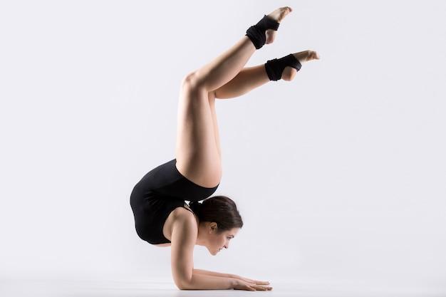 Junge frau macht akrobatische handstand übung