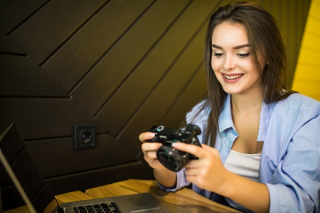 Junge frau macht ein bild auf retro-fotokamera, die im café sitzt