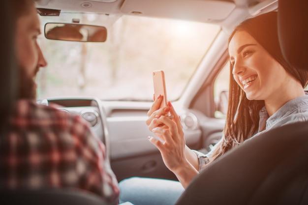 Junge frau macht foto von ihrem mann. sie schaut ans telefon und lächelt.