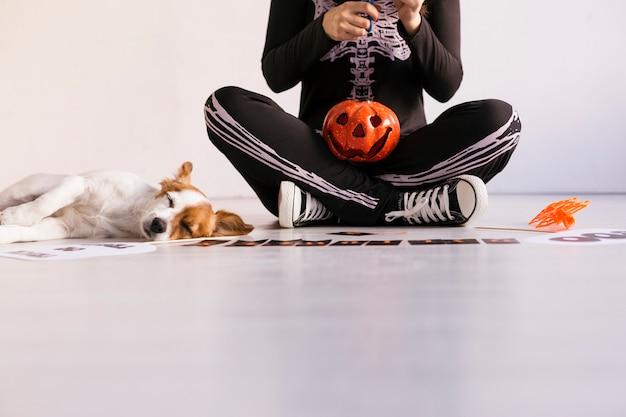 Junge frau macht halloween-girlande. kreative diy. wohnkultur projekt party.halloween handwerk inspiration. cuet kleiner hund außerdem