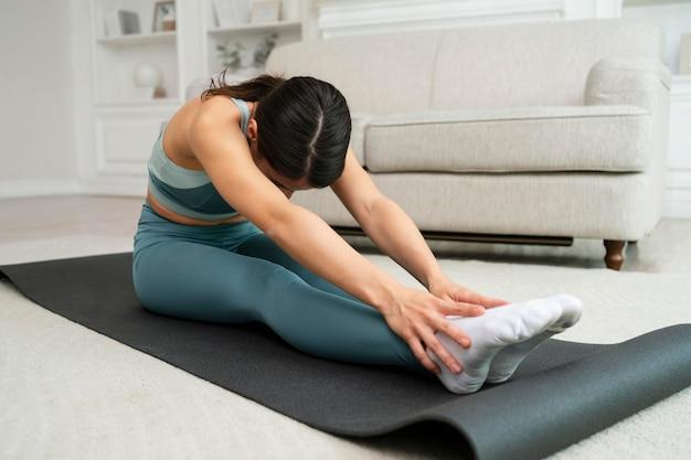 Junge frau macht ihr training auf einer fitnessmatte
