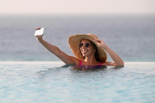 Junge frau macht im urlaub ein selfie mit ihrem smartphone
