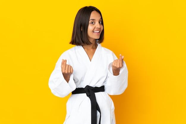 Junge frau macht karate isoliert auf gelbem hintergrund und macht geldgeste