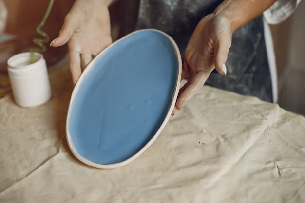 Junge frau macht keramik in der werkstatt