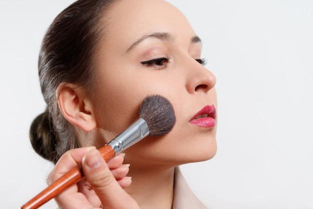 Junge frau macht make-up auf ihrem gesicht mit einem pinsel auf weiß