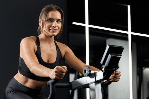 Junge frau macht sport im fitnessstudio