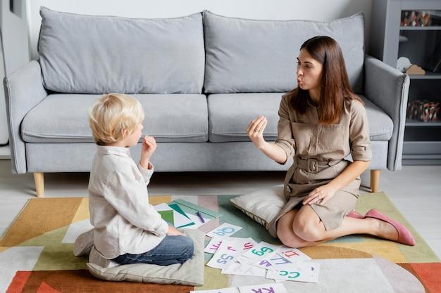 Junge frau macht sprachtherapie mit einem kleinen blonden jungen