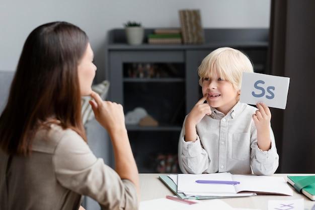Junge frau macht sprachtherapie mit einem kleinen jungen