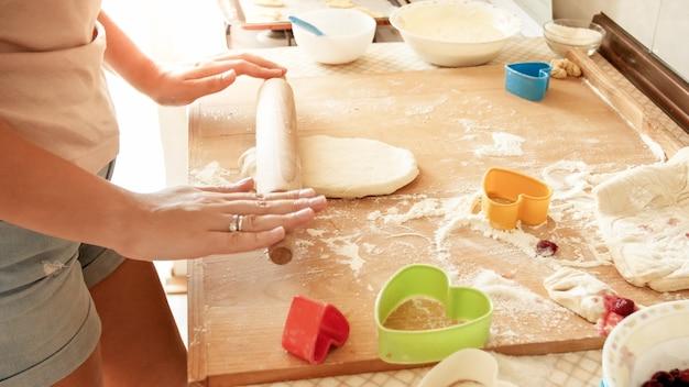 Junge frau macht teig und rollt ihn mit einem hölzernen nudelholz auf der küchentheke?
