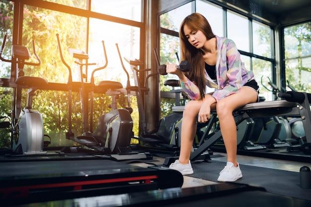 Junge frau macht übung im fitnessstudio
