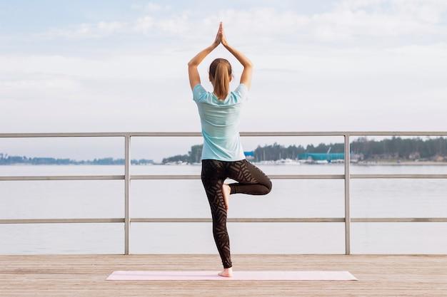 Junge frau macht yoga auf einem pier, der auf einem bein in der baumpose steht